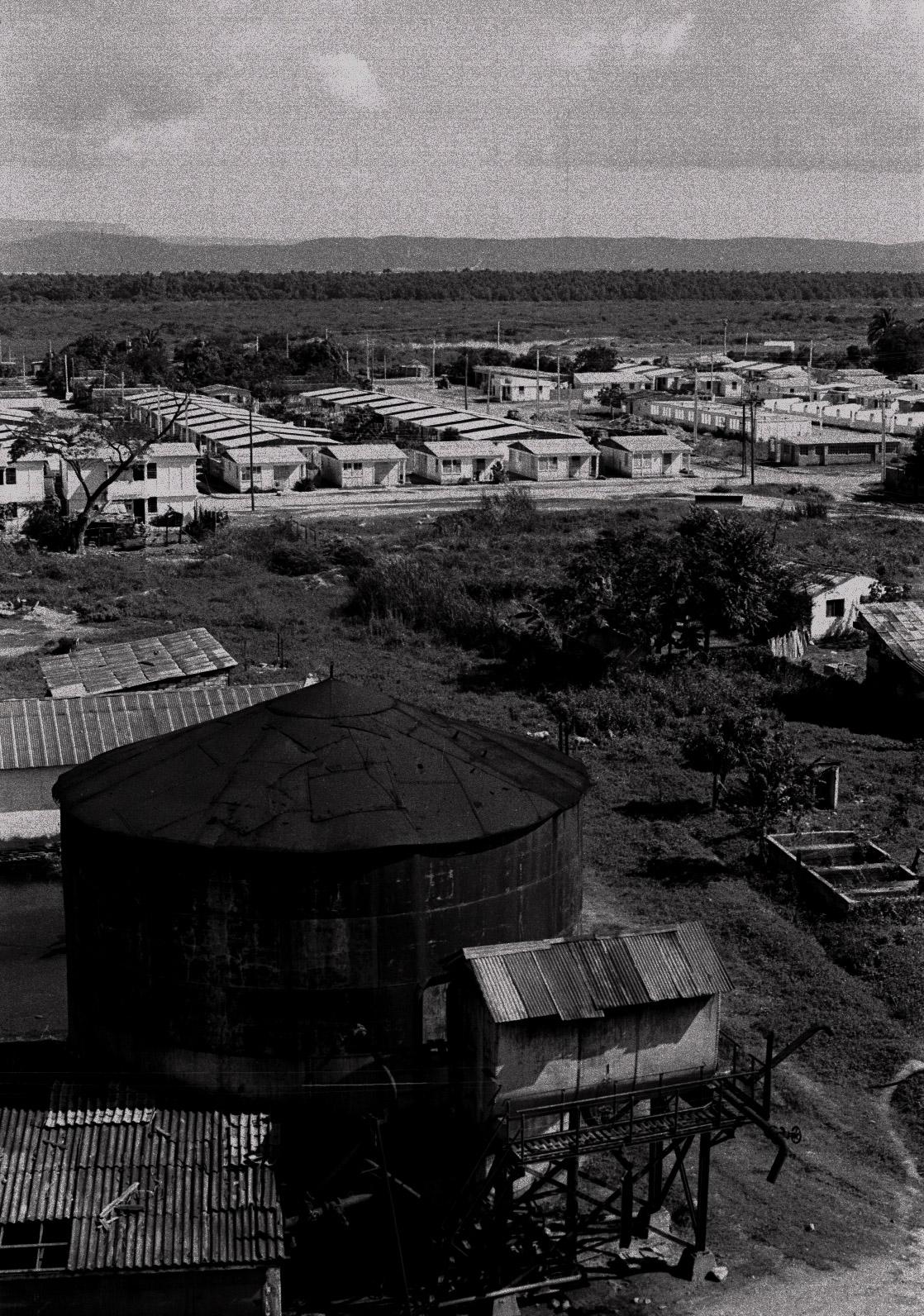 Vista aérea del Central Paraguay. Al fondo está la Base Naval de Guantánamo. El Central está en la segunda línea fronteriza con la Base. Las viviendas prefabricadas de los obreros sustituyeron los bohíos que a su vez habían desplazado a los barracones. (Foto: Alejandro Ramírez Anderson)
