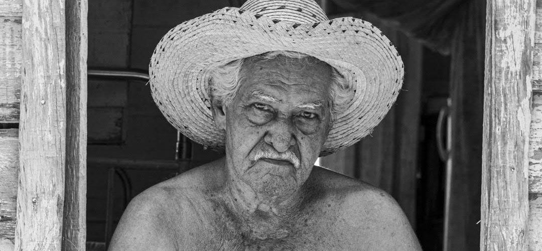 Alejandro Valdés Roy es un campesino de 83 años de edad. Vive en una casa alejada a varios kilómetros de la comunidad, con su esposa y uno de sus nietos. Dice Alejandro, que nunca desearía irse de su casa. Cuando pasó la última tormenta tropical por Pinar del Río, sus hijos, que hace tiempo emigraron hacia el pueblo (así nombran los habitantes del Hoyo a la ciudad de Pinar del Río), le pidieron que saliera del Hoyo, pero él se negó (Foto: Lázaro Lemus).